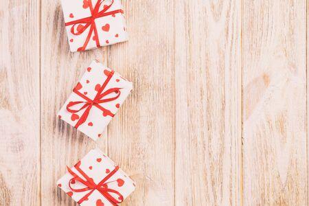 Regalo di San Valentino o altro regalo fatto a mano in carta con cuori rossi e scatola regalo in confezione natalizia. Presente scatola regalo su tavolo in legno arancione vista dall'alto con spazio copia, spazio vuoto per il design.