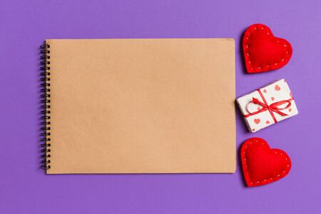Top view of craft notebook surrounded with gift box and hearts on colorful background. Valentine's Day concept. 免版税图像