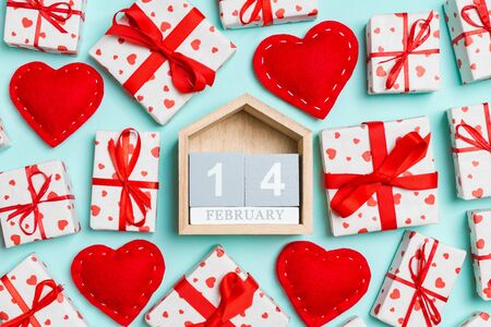 Composition of wooden calendar, holiday white gift boxes and red textile hearts on colorful background. The fourteenth of February. Valentine's day concept. Stock Photo - 137091061