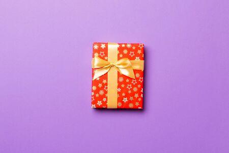 Confezione regalo con fiocco d'oro per Natale o Capodanno su sfondo viola, vista dall'alto con spazio per le copie.