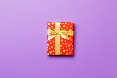 Gift box with gold bow for Christmas or New Year day on purple background, top view with copy space.