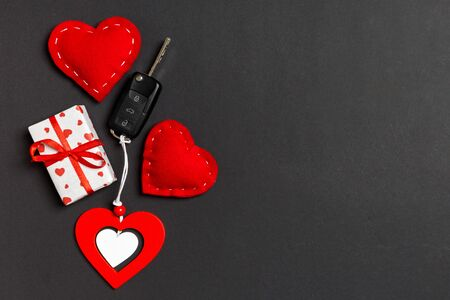 Top view of gift box, car key, wooden and textile heart on colorful background. Luxury present for Valentine's day. Reklamní fotografie