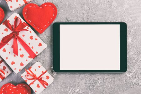 Digital tablet blank screen with gift box and hearts decor on gray cement table. Top view. Valentines Day concept background. Zdjęcie Seryjne