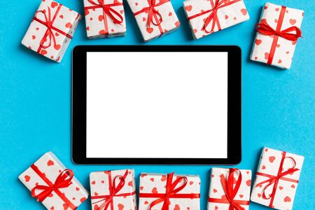 Top view of digital tablet surrounded with gift boxes on colorful background. Saint Valentines day.