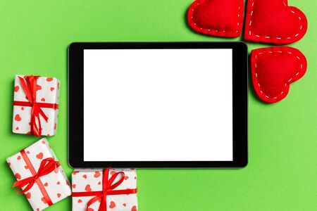 Top view of digital tablet surrounded with gift boxes and hearts on colorful background. Saint Valentines day.