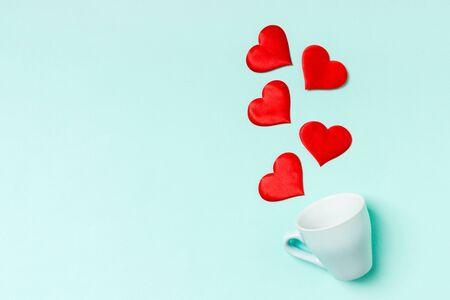 Draufsicht auf rote Textilherzen, die aus einer Tasse auf buntem Hintergrund spritzen. Happy Valentinstag-Konzept.