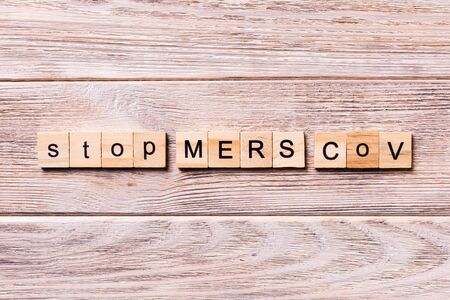 stop MERS CoV word written on wood block. stop MERS CoV text on wooden table for your desing, coronavirus concept top view. Archivio Fotografico