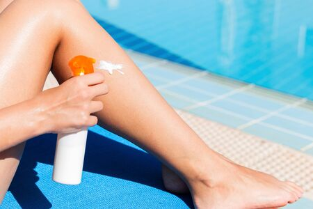 Young woman is applying sun cream on her smooth tanned legs by the pool. Sun Protection Factor in vacation, concept. 스톡 콘텐츠