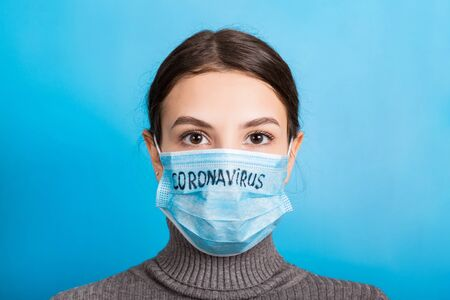 Portrait of a woman in medical mask with coronavirus text at blue background. Coronavirus concept. Respiratory protection.