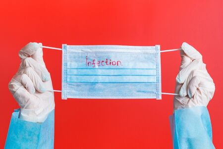 Female hands in medical gloves holding protective mask with infection word on it at red background. Health care concept. Coronavirus concept.