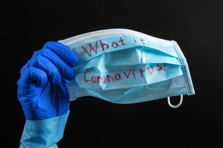 Hand in medical glove is showing protective mask at black background. What is coronavirus text on mask. Coronavirus concept. Healthcare concept.