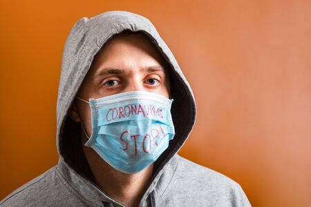 Portrait of young man in hood wearing protective medical mask with stop coronavirus text at brown background. Coronavirus concept. Healthcare concept. Stok Fotoğraf