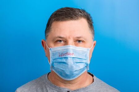 Portrait of a sick man wearing medical mask with infection text at blue background. Coronavirus concept. Protect your health. Stok Fotoğraf