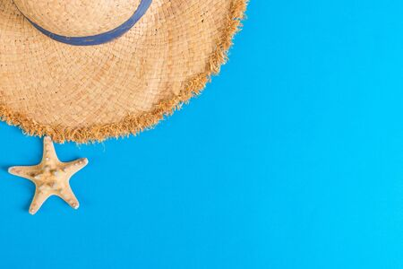 yellow retro straw hat with seastar top view with copy space. summer concept on blue background. Stock Photo