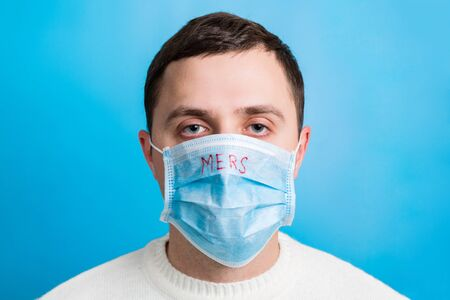 Portrait of a sick man wearing medical mask with MERS text at blue background. Coronavirus concept. Protect your health.
