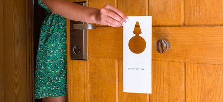 female hand hangs a sign on the door do not disturb in hotel. Foto de archivo - 140076851
