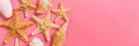 sea shells and starfish on a pink banner background and sand. Vacation time concept.