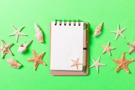 blank note book with starfish or seashells on a green background , summer vaction concept.
