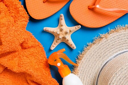 Summer beach flat lay accessories. Sunscreen bottle cream, straw hat, flip flops, towel and seashells on colored Background. Travel holiday concept with copy space. Stok Fotoğraf