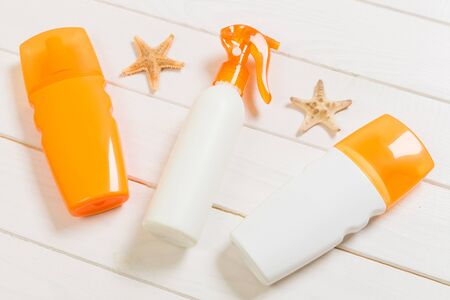 flat lay concept summer travel vacation. Sunscreen bottles with starfish on white wooden table with copy space. Stok Fotoğraf