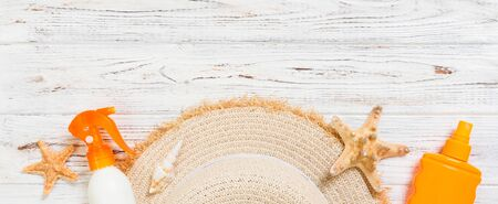Sunscreen bottles with starfish and sunhat on white wooden table banner with copy space. Travel healthcare accessories top view. Stok Fotoğraf