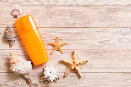 sun protection cream bottle and seashells on wooden background with copy space. flat lay concept of summer travel vacation.