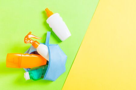 Top view of female cosmetics bag full of suncream spray, sunsreen, sunblock and body lotion and spf cream on yellow and green background with copy space. Directly above. Bright summer concept.