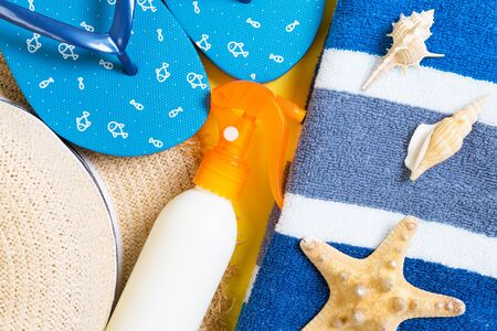 flip flops, straw hat, starfish, sunscreen bottle, body lotion spray on yellow background top view . flat lay summer beach sea accessories background, vacation concept. Stok Fotoğraf
