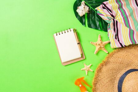 Summer accessories with t-shirt, seashells, flip flops sunscreen bottle and straw hat on green background top view flat lay.