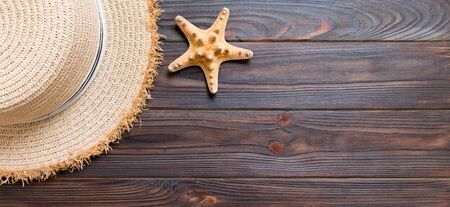 Straw hat and starfish On a dark banner wooden background. top view summer holiday concept with copy space. Stok Fotoğraf