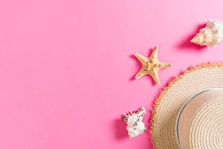 Beach hat with seashells on pink wooden table. summer background concept with copy space top view. Stok Fotoğraf