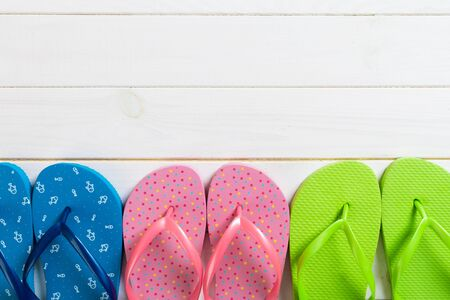 a lot of flip flop colored sandals, summer vacation on wooden background, copy space top view.