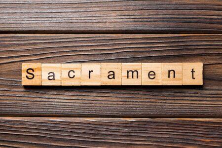 sacrament word written on wood block. sacrament text on table, concept. 版權商用圖片