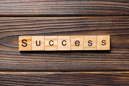 Success word written on wood block. Success text on table, concept.