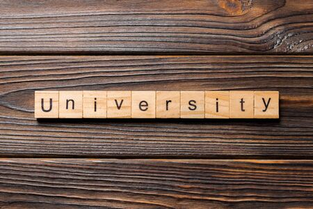 UNIVERSITY word written on wood block. UNIVERSITY text on wooden table for your desing, concept.