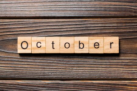 October word written on wood block. October text on wooden table for your desing, Top view concept.