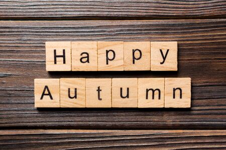 Happy autumn word written on wood block. Happy autumn text on wooden table for your desing, concept.