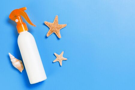 sunscreen cream with starfish and seashells in bottles on blue background, top view.