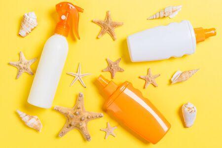 Sunscreen bottles with seashells on yellow wooden table. Stok Fotoğraf