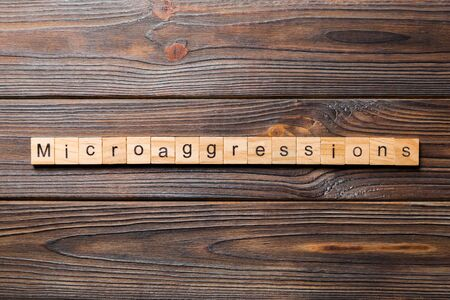 Microaggressions word written on wood block. Microaggressions text on wooden table for your desing, concept.