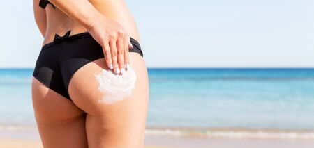 Woman hand is applying suntan cream on her buttocks at the beach at the sea background. Stok Fotoğraf