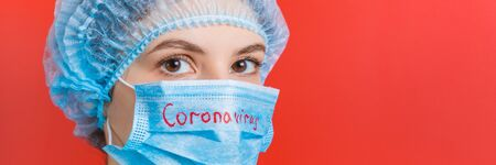 Portrait of a woman wearing medical uniform and mask with coronavirus word at red background. Coronavirus concept. Respiratory protection concept with copy space.