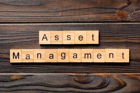 Asset management word written on wood block. Asset management text on wooden table for your desing, Top view concept.