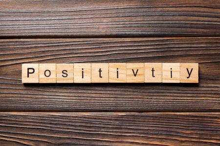 positivity word written on wood block. positivity text on wooden table for your desing, concept.