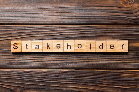 Stakeholder word written on wood block. Stakeholder text on wooden table for your desing, concept.