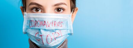 Portrait of a woman in medical mask with stop coronavirus text at blue background. Coronavirus concept. Respiratory protection.