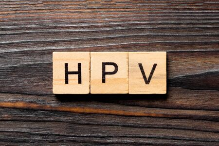 HPV word written on wood block. HPV text on wooden table for your desing, Top view concept. Stock Photo