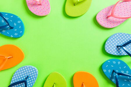 a lot of flip flop colored sandals, summer vacation on colored background, copy space top view. Reklamní fotografie