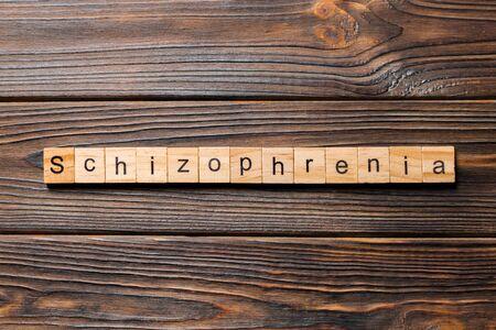 schizophrenia word written on wood block. schizophrenia text on table, concept.
