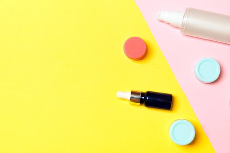 Group of plastic bodycare bottle Flat lay composition with cosmetic products on yellow and pink background empty space for you design. Set of White Cosmetic containers, top view with copy space.